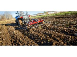 A farmer using a mounted ATV cultivator to farm the land